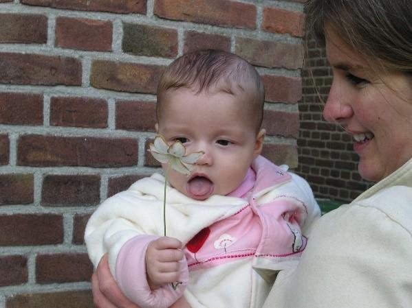 Afbeelding met persoon, baby, vasthouden, zitten  Automatisch gegenereerde beschrijving